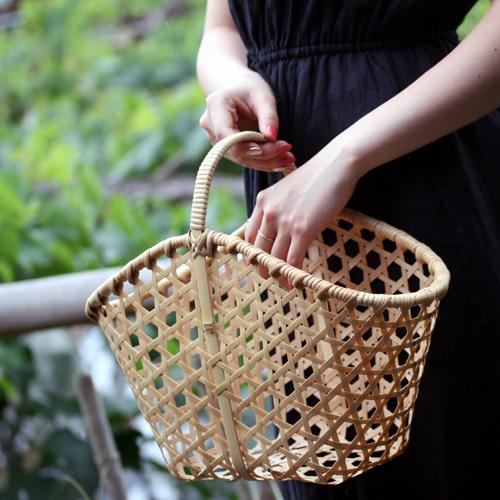 竹バッグを持っている女性