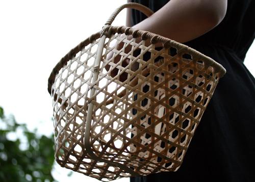 竹細工のかごを持つ女性
