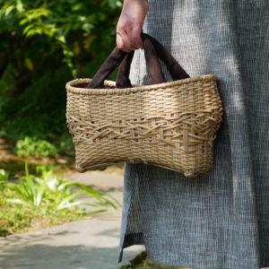 ナチュラルカラーの竹バッグを持つ女性