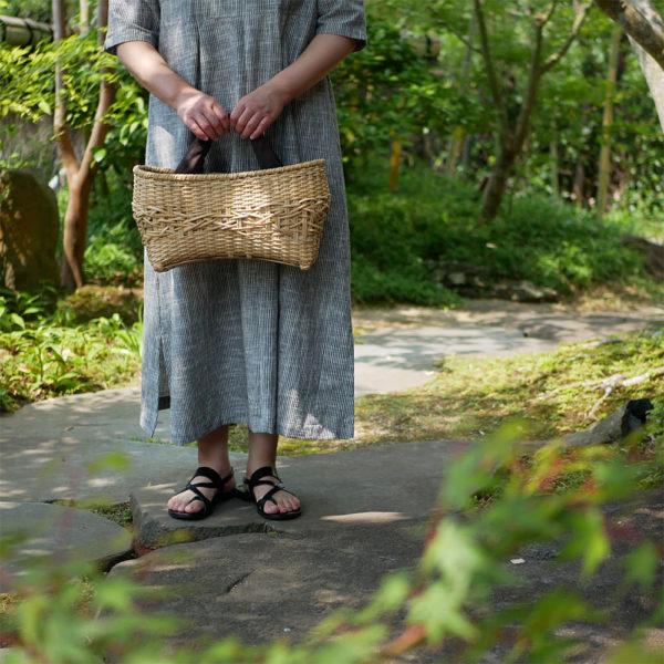 ナチュラルカラーの竹バッグを持つ女性2