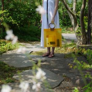 黄色の竹バッグを持つ女性