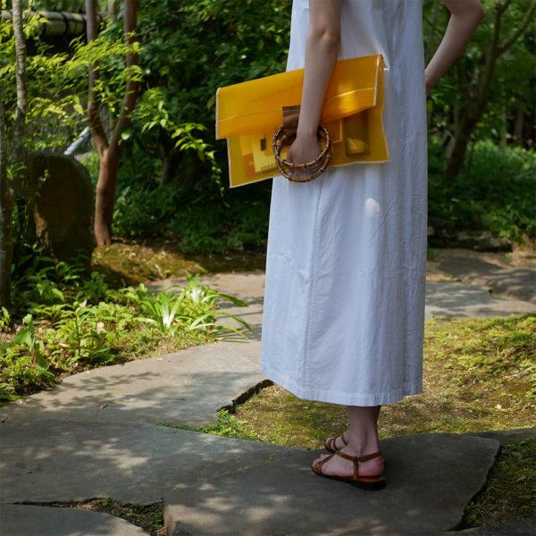 黄色の竹のクラッチバッグを持つ女性