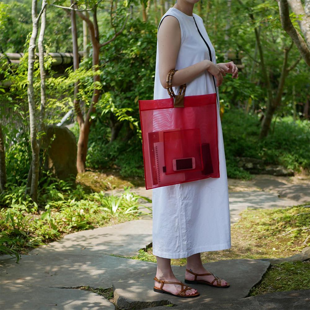 赤色の竹バッグを持つ女性