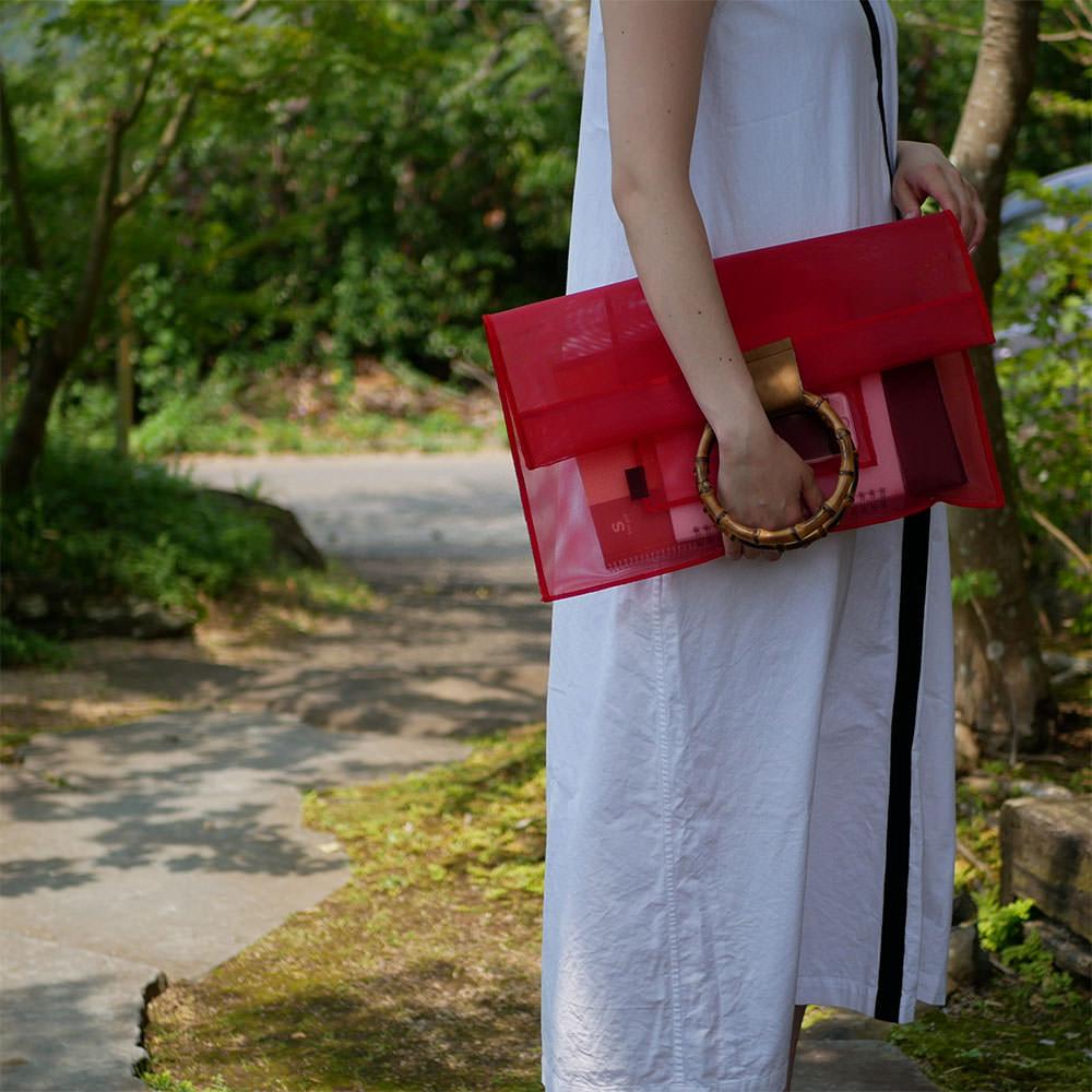 赤色の竹クラッチバッグを持つ女性