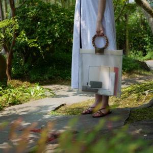 ベージュの竹バッグを持つ女性