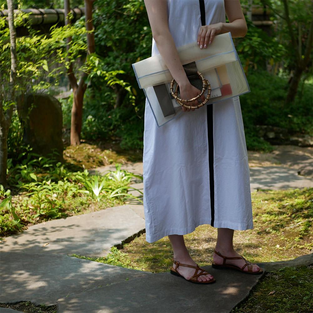 ベージュの竹のクラッチバッグを持つ女性
